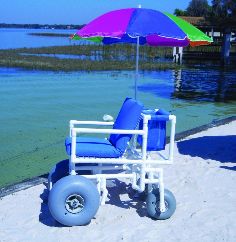 Cadeira de rodas anfíbia, com guarda-sol colorido,  em estrutura de canos de PVC brancos, almofadas no encosto azuis e grande e largas rodas azuis claras. A areia é verde e fofa e água verde, cristalina e calma.