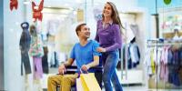 Em um shopping, um homem de cabelos curtos, camisa azul e calça bege está em uma cadeira de rodas, empurrado por uma mulher de cabelos castanhos claros compridos, de camisa roxa e calça jeans. Os dois estão sorrindo. Fim da descrição.