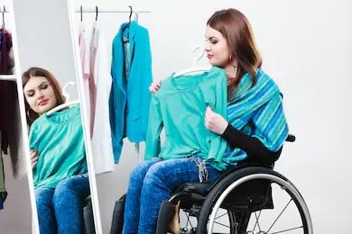 #ParaTodosVerem: mulher em sua cadeira de rodas experimentando roupas em frente ao espelho. As roupas são todas em tons de azul. A mulher é morena, com batom vermelho e cabelos longos, blusa de manga comprida preta e calça jeans. Fim da descrição.