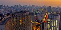 Foto panorâmica da cidade de São Paulo ao entardecer com destaque para o Edifício Copan.