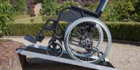 Rampa modular antiderrapante na cor preta. Há uma canaleta de proteção nas laterais e dobradiças para facilitar o acesso da cadeira de rodas. Montada numa calçada com degrau e há uma cadeira de rodas vazia por cima. Fim da descrição.