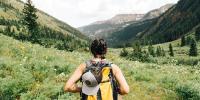 Homem de costas com mochila contemplando um vale com montanhas e árvores.